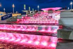 Die belichtete Wasserfallkaskade am Olympiapark verzaubert mit seinem schönen Spiel des Wassers und des Lichtes Stockfotos