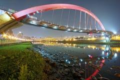Die berühmte Regenbogen-Brücke über Keelungs-Fluss mit Reflexionen auf glattem Wasser an der Dämmerung in Taipeh, Taiwan, Asien Stockfotos