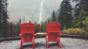 Die berühmten roten Stühle, die Takakkaw gegenüberstellen, fällt in Kanada Lizenzfreie Stockfotografie