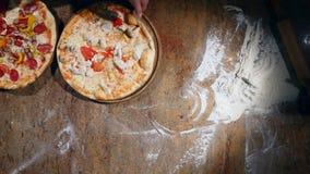 Die bereite Pizza, die vom Ofen erhält und setzt sich auf dem Tisch stock video footage