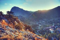 Die Berge und das Dorf bei Sonnenuntergang Blauer Himmel und blanke Hügel Natur Stockfotos