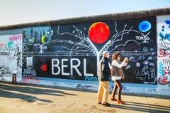 Die Berliner Mauer (Bewohner von Berlin Mauer) mit Graffiti Stockfotografie