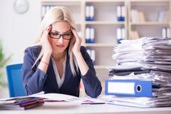 Die beschäftigte Geschäftsfrau, die im Büro am Schreibtisch arbeitet lizenzfreie stockfotos