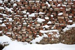 Die Beschaffenheit der alten Backsteinmauer, mit einer starken Schneeschicht nach schwere Schneefälle umfasst Stockfotografie