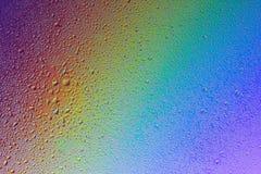 Die Beschaffenheit der Tröpfchen auf dem Glas auf Regenbogenhintergrund Stockbild
