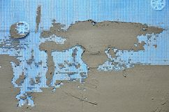 Die Beschaffenheit der Wand, umfasst mit grauen Schaumpolystyrenplatten, umfasst mit einer blauen Verstärkungsmasche und mit eine Lizenzfreie Stockfotos