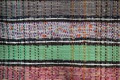 Die Beschaffenheit des handgemachten Teppichs gemacht auf Handwebstuhl mit vier verschiedenen Farben teilte sich mit vertikalen D Stockbild