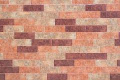 Die Beschaffenheit einer Backsteinmauer der dekorativen mehrfarbigen rechteckigen Ziegelsteine mit Geräuschen, Kratzer lizenzfreie stockfotos