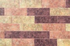 Die Beschaffenheit einer Backsteinmauer der dekorativen mehrfarbigen rechteckigen Ziegelsteine mit Geräuschen, Kratzer stockbilder