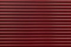Die Beschaffenheit einer Metallrolle der verschiedenen Farben Der Hintergrund der Eisenvorhänge Schützende Rollenfensterläden für Stockfotografie