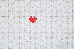 Die Beschaffenheit eines weißen Puzzlen in einem zusammengebauten Zustand mit einem fehlenden Element, das einen roten Raum bilde lizenzfreie stockbilder