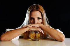 Die betrunkene alkoholische Frau vergeudete das Lehnen niedergedrückt auf Glas des schottischen Whiskys Stockfoto