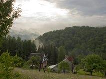 Die bewaldeten Berghänge im Nebel unter dem Morgen sonnen thro Lizenzfreie Stockbilder
