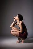 Die bezaubernde verleitende Discalced Frau, die auf ihr sitzt, bückt sich in Träumerei. Tagtraum Lizenzfreies Stockfoto