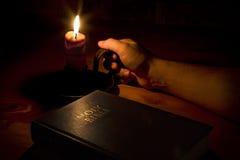 Die Bibel durch Kerzeleuchte Stockfotografie