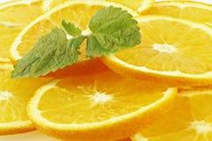 Die Blätter der Minze liegend auf orange Segmenten. Lizenzfreie Stockbilder