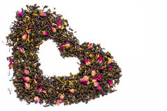 Die Blätter des grünen Tees mit den rosafarbenen Knospen und Scheiben von Trockenfrüchten und von wilden Blumen mit den Blumenblä Stockbild