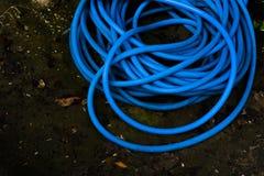 Die blaue Plastikwasserleitung gesetzt auf nass Boden lizenzfreies stockbild