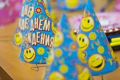 Die blauen und gelben Papiergeburtstagskappen auf dem Tisch Stockfotografie