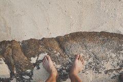 Die bloßen Füße des Mannes, die am hölzernen Dock stehen Lizenzfreie Stockfotos
