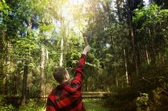 Die Blockwinde in einem roten karierten Hemd hält eine Axt gegen den Wald Stockfotos