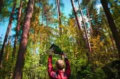 Die Blockwinde in einem roten karierten Hemd hält eine Kettensäge gegen den Wald Stockfotografie