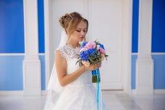 Die blonde Braut steht auf einem blauen und blauen Gebäude in einem Hochzeitskleid und genießt das Aroma eines Blumenstraußes der Lizenzfreies Stockfoto