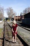 Die blonde Frau, die auf Eisenbahn steht, spürt rotes Kleid auf Stockfotos
