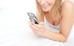 Die blonde Frau, die eine Textmeldung sich hinlegt auf gibt, ist Stockbilder