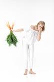Die blonde Frau, die Karotte mit Grün hält, verlässt auf weißem Hintergrund Mädchen fühlt sich von den Karotten schlecht und nähr Stockbilder