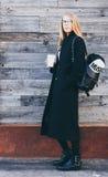Die blonde Frau, die schwarzen Mantel tragen, die Hippie-Gläser und das Rucksacktrinken nehmen Kaffee in der Papierschale weg, di Stockfoto