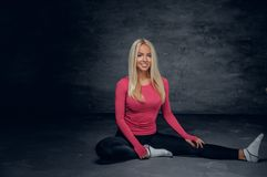 Die blonde Frau, die in einem rosa Trikot gekleidet wird, sitzt auf einem Boden Lizenzfreies Stockfoto