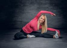 Die blonde Frau, die in einem rosa Trikot gekleidet wird, sitzt auf einem Boden Stockfotos