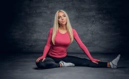 Die blonde Frau, die in einem rosa Trikot gekleidet wird, sitzt auf einem Boden Stockfotografie