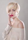 Die blonde Frau mit dem kurzen Haar berührt die Lippen Stockfoto