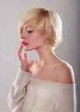 Die blonde Frau mit dem kurzen Haar berührt die Lippen Lizenzfreie Stockfotos