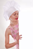 Die blonde Frau mit dem kurzen Haar in einem Hut und in einem Koch mit dem schönen Lächeln, das eine weiße Anschlagtafel hält Stockfoto