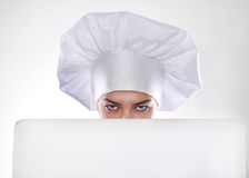 Die blonde Frau mit dem kurzen Haar in einem Hut und in einem Koch mit dem schönen Lächeln, das eine weiße Anschlagtafel hält Stockbilder