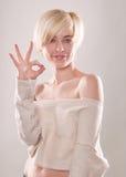 Die blonde Frau mit dem kurzen Haar und einem schönen Lächeln mit dem Zeigefinger lokalisiert Stockfotografie
