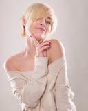 Die blonde Frau mit dem kurzen Haar und einem schönen Lächeln mit dem Zeigefinger lokalisiert Stockfotos