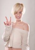 Die blonde Frau mit dem kurzen Haar und einem schönen Lächeln mit dem Zeigefinger lokalisiert Lizenzfreies Stockfoto