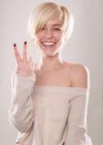 Die blonde Frau mit dem kurzen Haar und einem schönen Lächeln mit dem Zeigefinger lokalisiert Stockfoto