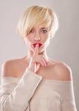 Die blonde Frau mit dem kurzen Haar und einem schönen Lächeln mit dem Zeigefinger lokalisiert Lizenzfreie Stockbilder