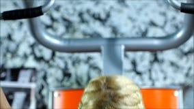 Die blonde Frau mit roten kurzen Hosen und schwarzen Spitzenübungen auf der Turnhallenausrüstung stock video