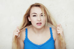 Die blonde Frauenjugendliche, die sie zeigt, beschädigte trockenes Haar Stockfotos