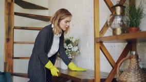 Die blonde Hausfrau, die schützende Gummihandschuhe trägt, wischt eine Tabelle ab zu Hause, die Hausarbeit tut Kopfhörer, Treppen stock video footage