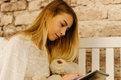 Die blonde Jugendliche hält die Tablette und den Teddybären Weiche Farben Stockbild