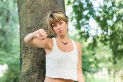 Die blonde junge Frau, die draußen Daumen unterzeichnen tut unten Stockfotografie