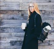 Die blonde junge Frau, die schwarzen Mantel tragen, die Hippie-Gläser und das Rucksacktrinken nehmen Kaffee in der Papierschalens Lizenzfreie Stockbilder