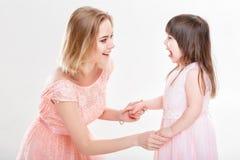 Die blonde Mutter, die Tochter im Rosa tröstet, kleidet Prinzessinnen Baby Lizenzfreies Stockfoto